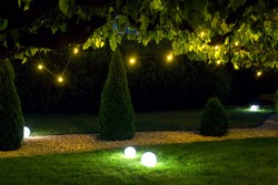 illumination park light garden with electric ground ball lantern with stone mulch and thuja bushes in outdoor landscaped park with garland of warm light bulbs, illuminate evening scene nobody.