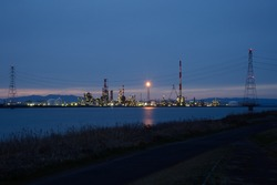 Illuminations of a factory along the coast on a winter night.  Focused on the factory.  The foreground is slightly blurred.