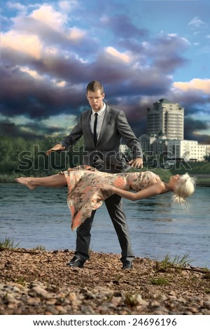 Illusionist. A handsome confident man keeps a young lady levitating in the air.