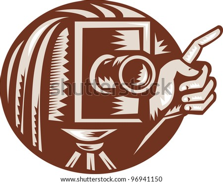 Illustration of a vintage bellow camera with hand pointing done in retro woodcut style set inside circle.
