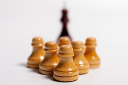 Illustration of chess pieces. The black king with blurred forms and white pawns with a clear outline in the foreground.