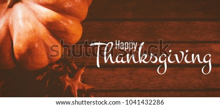 Illustration of happy thanksgiving day text greeting against pumpkin by autumn leaves on wooden table