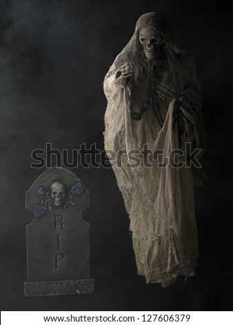 Illustration of Standing Grim reaper and Spooky Tombstone in a vertical image
