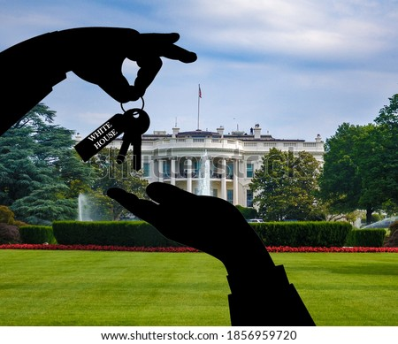 Photo of  Illustration of the concept of presidential transition after elections before taking over the administration of the federal government. Passing white house keys with blurred capitol in background