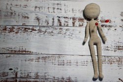 illustration of unhappy love - faceless knitted human figure with red knitting pin studded in heart