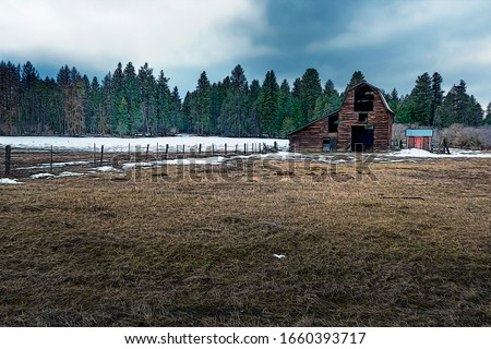 Illustration of Wood barn in a snow field along the barbed wire fence with snow on the winter ground