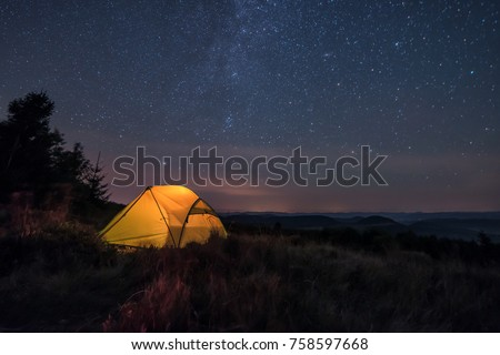 iluminated tent under stars in the mountains