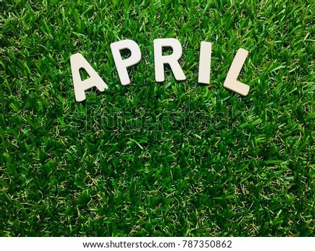 Image April, wooden alphabet April on green grass background with copy space for your text. Concept be used for calendar, month and background. Blur picture and exposure.