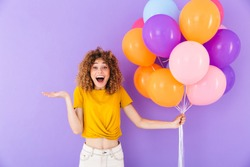 Image closeup of attractive delighted woman rejoicing while posing in multicolored air balloons isolated over violet background