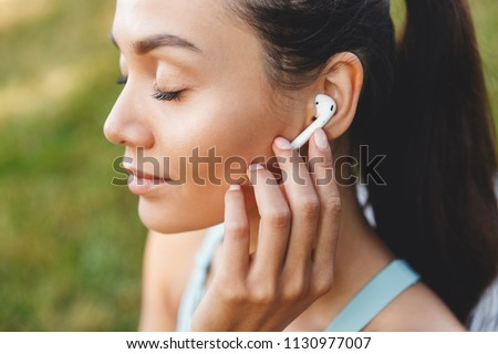 Image closeup of beautiful joyful woman 20s in sportswear using bluetooth earbud and listening to music with closed eyes during walk in green park