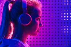 Image closeup of beautiful young caucasian woman listening to music with headphones over purple neon illumination indoors
