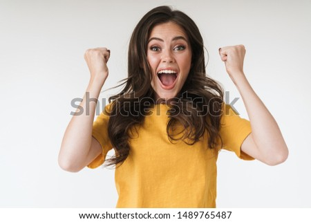 Image closeup of happy brunette woman wearing casual t-shirt screaming and clenching fists isolated over white background Foto stock ©