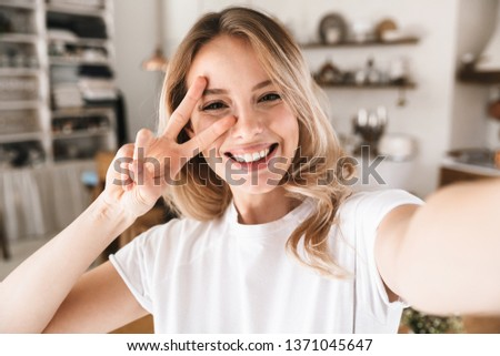 Image closeup of pleased blond woman 20s wearing white t-shirt smiling while looking at camera and taking selfie photo in living room