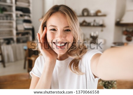 Image closeup of stylish blond woman 20s wearing white t-shirt smiling while looking at camera and taking selfie photo in living room