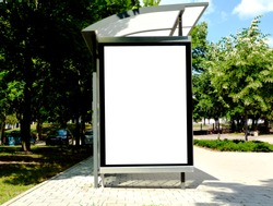 image composite of bus shelter at bus stop of blank light box and glass structure. park-like urban setting. green background. safety glass design. white poster ad commercial poster space display glass