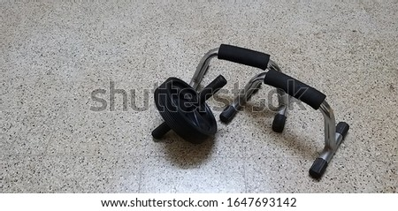 Image contains an ab wheel and a pair of push ups handle on a spotted flooring