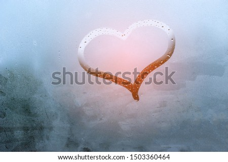Image drawing a heart. Drawn with a finger on wet glass. Close up and horizontal orientation.  #1503360464