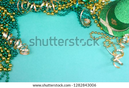 Image for Saint Patrick's Day on March 17th. A border of green and gold ribbons and beads and a sparkly leprechaun  hat on green. Copy space.