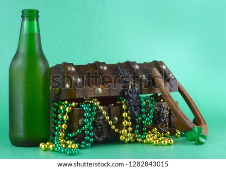 Image for Saint Patrick's Day on March 17th. Treasure chest to symbolize luck and wealth. A bottle of beer and a lucky horseshoe are added. Copy space.