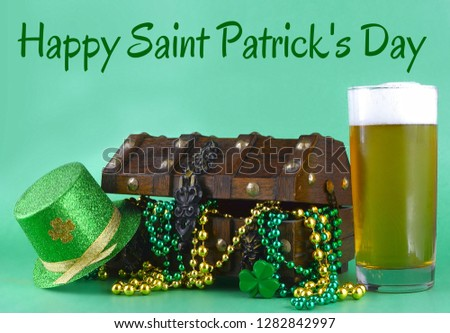 Image for Saint Patrick's Day on March 17th. Treasure chest to symbolize luck and wealth. A glass of beer and a sparkly leprechaun hat has been added with holiday greeting text.