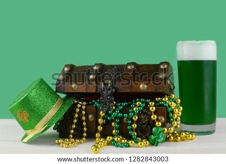 Image for Saint Patrick's Day on March 17th. Treasure chest to symbolize luck and wealth. A glass of green beer and a sparkly leprechaun hat are added. Copy space