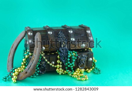 Image for Saint Patrick's Day on March 17th. Treasure chest to symbolize luck and wealth filled with shiny green and gold beads. A lucky horseshoe is shown. Copy space