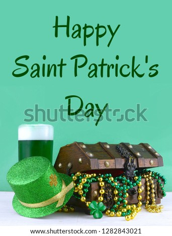 Image for Saint Patrick's Day on March 17th. Treasure chest to symbolize luck and wealth. Vertical image with green beer and sparkly leprechaun hat. Holiday greeting message added.