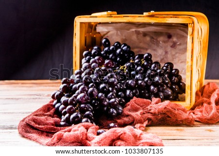 Image from above of black grapes in wooden basket with claret cloth on table in studio #1033807135
