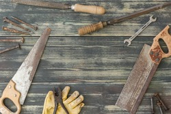 image from above of old tools on dark wood background scattered around image with negative space in center with natural light