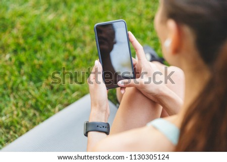 Image from back of sporty european woman 20s in sportswear resting in green park and using cell phone with bluetooth earpod