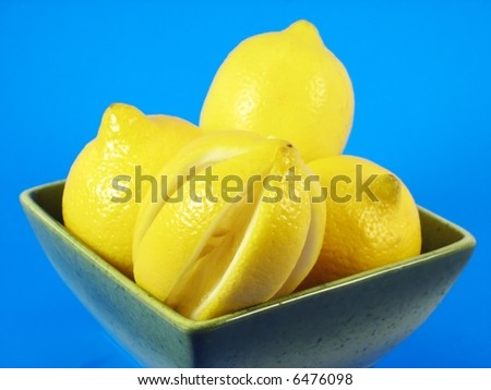 image from fruits series: lemons in green bowl in green bowl on blue background