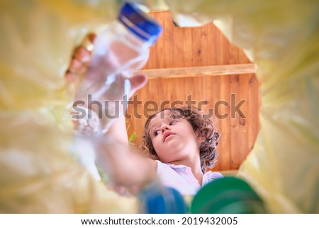 image from inside a recycling bin with a yellow bag of a girl throwing a plastic bottle to recycle in which the bottles are out of focus Photo stock ©
