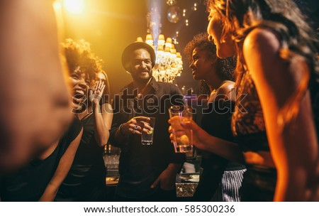 Image group of friends enjoying a party at pub. Happy young people having fun at nightclub.