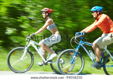 Image in motion of two bicyclists riding on country road