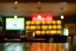 Image is blurred in a bar or tavern. Abstract image of an alcoholic beverage shop or pub. Colorful lighting in a store selling beer, alcohol, cocktails and a wide variety of beverages.