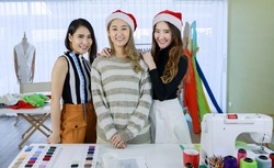 Image is portrait. Smiling Asian young woman 3 Three standing taking pictures to promote the tailor shop. Concept Designer new product and my friend