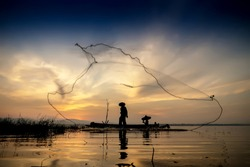 Image is silhouette. Fishermen Casting are going out to fish early in the morning with wooden boats, old lanterns and nets. Concept Fisherman's life style