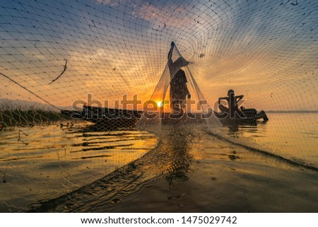 Image is silhouette. Fishermen Casting are going out to fish early in the morning with wooden boats, old lanterns and nets. Concept Fisherman's life style.