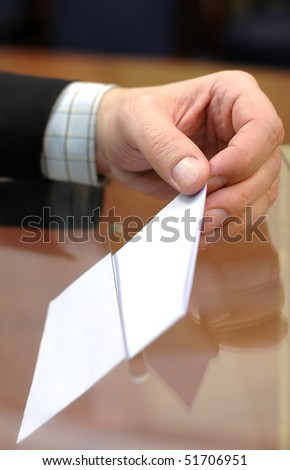 image of a ballot box and hand putting a blank ballot inside