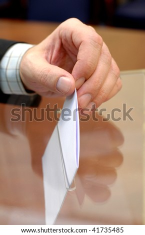 image of a ballot box and hand putting a blank ballot inside, elections concept, voting concept , - stock photo