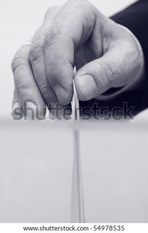 image of a ballot box and hand putting a blank ballot inside, elections concept, voting concept , blue toned