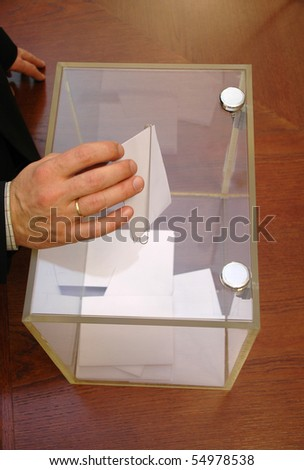 image of a ballot box and hand putting a blank ballot inside, elections concept, voting concept ,