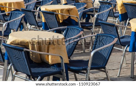 Image of a beautiful and bicolor Venetian street restaurant terrace with rattan chairs.