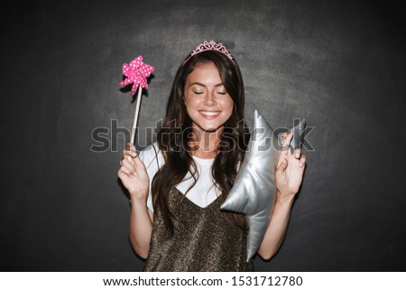 Image of a beautiful cute emotional girl with pillow and toy magic wand isolated over chalkboard grey background make hopeful please gesture.