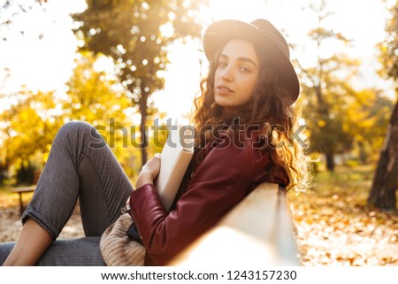 Image of a beautiful cute woman sitting on a bench in park reading book. #1243157230