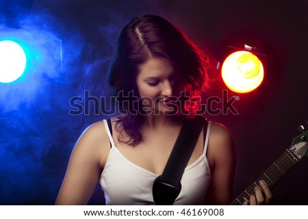 Image of a beautiful girl with a guitar in the spotlight