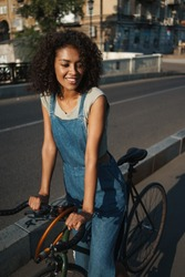 Image of a beautiful happy positive young african woman walking outdoors with bicycle by street.