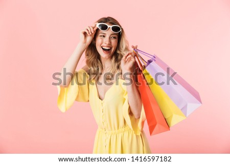 Image of a beautiful happy young blonde woman posing isolated over pink wall background holding shopping bags.