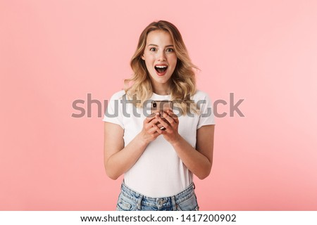 Image of a beautiful shocked young blonde woman posing isolated over pink wall background using mobile phone.