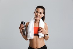 Image of a beautiful strong happy cheerful young sports woman posing isolated indoors drinking water with towel on neck.
